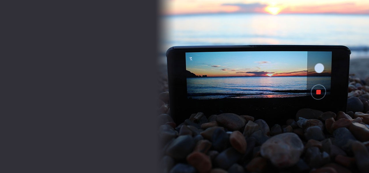 Mobile phone on the shore of a beach at sunset