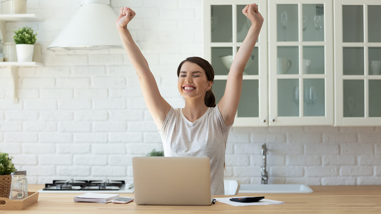 Photo of an woman responding to good news she read on her laptop